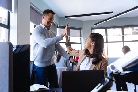 Photo pour Side view of a a mixed race woman and a Caucasian man wearing smart clothes, working in a modern office, smiling and hi fiving, with other colleagues working in the background.  - image libre de droit