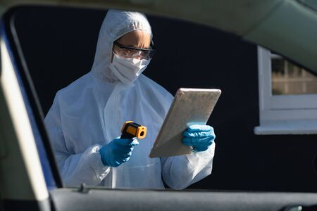 Foto de Caucasian woman wearing lab overalls and a face mask face standing outside by a car, using tablet and holding thermometer - Imagen libre de derechos