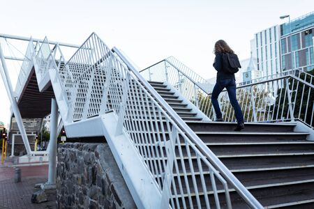Photo pour Caucasian woman out and about in the city streets during the day, walking up stairs on a bridge with her backpack on - image libre de droit