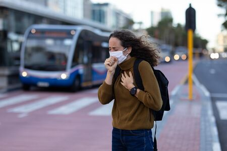 Photo pour Caucasian woman out and about in the city streets during the day, wearing a face mask against covid19 coronavirus covering her face while coughing - image libre de droit