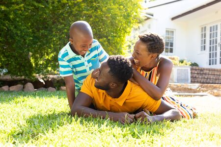 Foto de African American woman spending time with her partner and their son, lying on a lawn in the garden. Social distancing and self isolation in quarantine lockdown. - Imagen libre de derechos