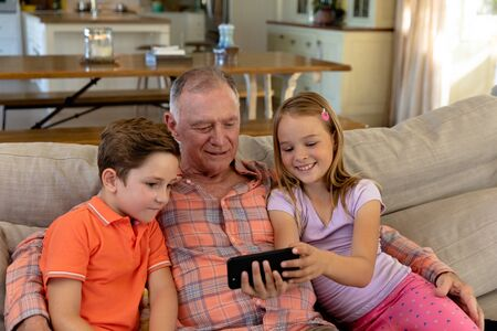 Photo pour Front view of a senior Caucasian man at home in the living room sitting on the couch with his grandson and granddaughter, looking at a smartphone that the granddaughter is holding together - image libre de droit
