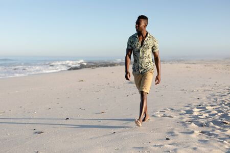 Photo for Attractive African American man enjoying free time on beach on a sunny day, wearing a Hawaiian shirt, walking on the beach sun shining on his face. Relaxing summer vacation. - Royalty Free Image