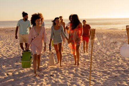 Photo pour A multi-ethnic group of friends enjoying their time together on a beach on a sunny day, walking barefoot, talking to each other - image libre de droit
