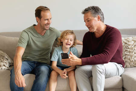 Photo pour Senior caucasian grandfather on couch looking at smartphone with adult son and grandson laughing. happy three generation family spending time together at home. - image libre de droit