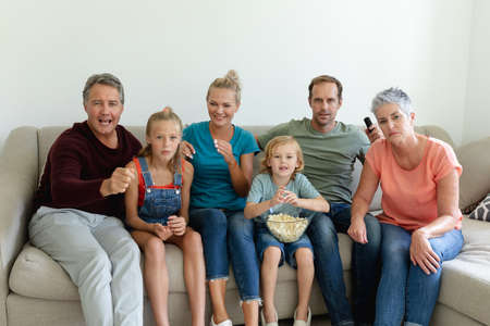Photo pour Caucasian parents, grandparents and grandchildren sitting on couch watching tv. happy three generation family spending time together at home. - image libre de droit