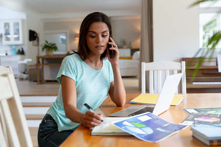 Photo for Caucasian woman sitting by desk working from home talking on smartphone and using laptop. staying at home in isolation during quarantine lockdown. - Royalty Free Image
