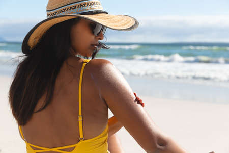 Photo for Mixed race woman on beach holiday using sunscreen cream. vacation outdoor leisure time by the sea. - Royalty Free Image