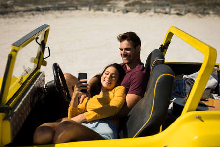 Photo pour Happy caucasian couple sitting in beach buggy by the sea relaxing. beach break on summer holiday road trip. - image libre de droit