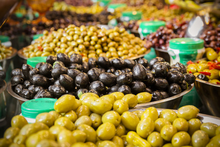 Olives at a market stall. A variety of types of olives. Green, black, Syrians and others.