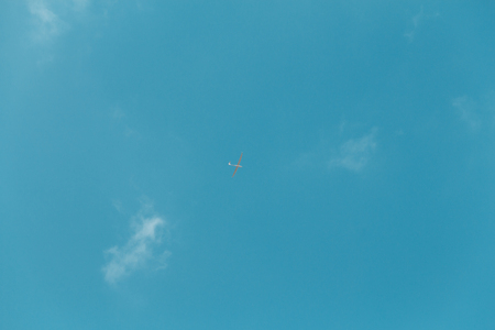 Glider gliding in blue sky from below.