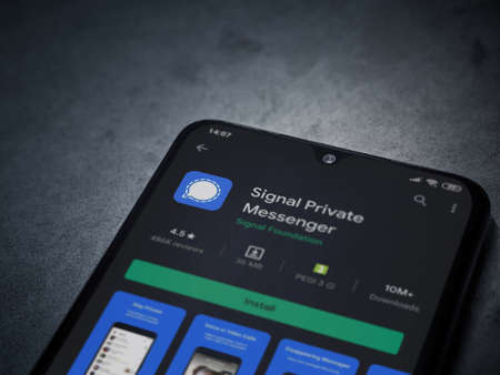 Lod, Israel - July 8, 2020: Signal Private Messenger app play store page on the display of a black mobile smartphone on dark marble stone background. Top view flat lay with copy space.