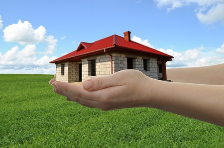 House in hands with green field and blue sky in  background