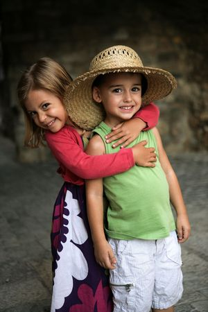 A young girl puts her arm around her friend and gives him a hug