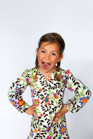 Studio portrait of young girl screaming and standing with her hands on hips
