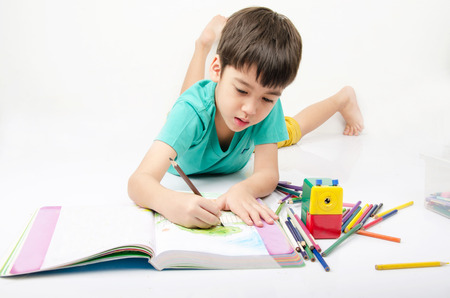 Little boy coloring image lay on th floor