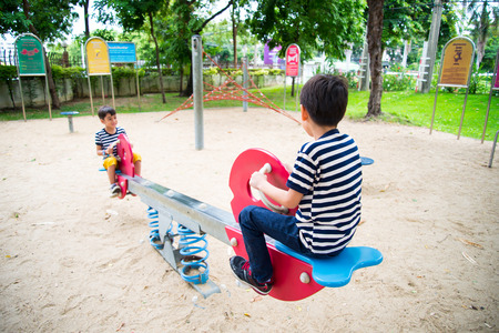 Little boys playing seesaw together in the park