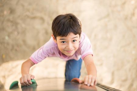 Photo pour Little boy climping up brave at playground - image libre de droit