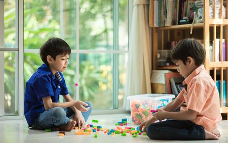 Foto de Little sibling  boy playing block indoor house education - Imagen libre de derechos