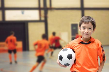 Foto de Little boy holding football in futsal gym - Imagen libre de derechos