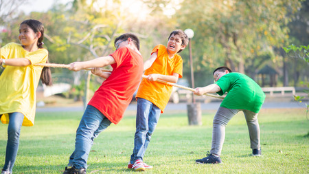 Photo for Asian students girls and boys play tug of war - Royalty Free Image