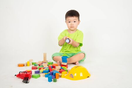 Photo pour Little Asian toddler boy playing wood blocks wear helmet engineer - image libre de droit