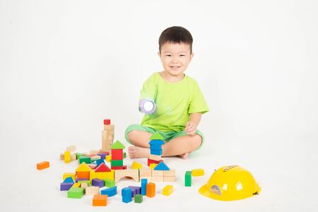 Foto de Little Asian toddler boy playing wood blocks wear helmet engineer - Imagen libre de derechos