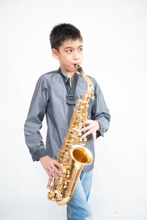 Foto de Little asian musician boy playing saxophone instrument - Imagen libre de derechos