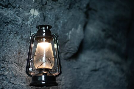 Photo for Oil lamp hanging on the cave stone wall - Royalty Free Image