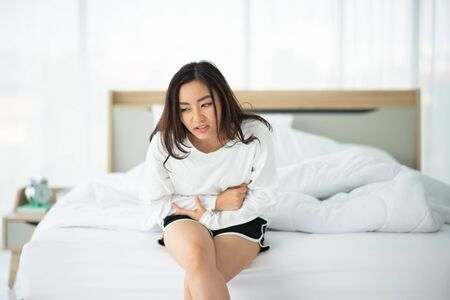 Photo pour Asian woman have stomachache in the morning at bedroom - image libre de droit