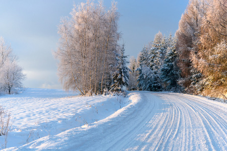 Winter landscape - snow covered mountain road on a cold and sunny morningの写真素材