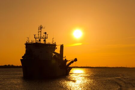 Photo for A work ship on the Elbe near Hamburg in the sunset - Royalty Free Image