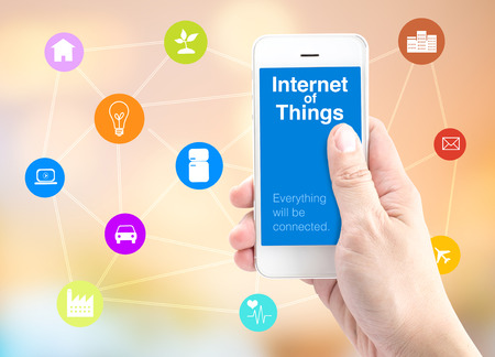 Hand holding smartphone with Internet of things (IoT) word and object icon and blur background, Digital Marketing concept.