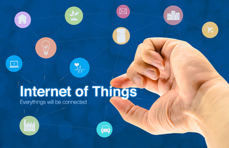 Hand holding Internet of things (IoT) word and object icon and blur background, Networking concept