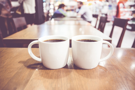 Vintage filter, couple of White coffee cup on wood table with blurred cafe bokeh light background.