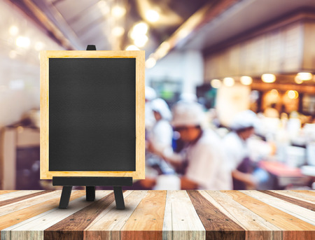 Blackboard menu with easel on wooden table with blur open kitchen at  restaurant background, Copy space for adding your content.