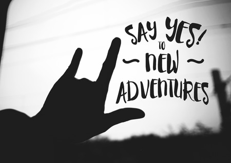 Inspiration quote : Say yes to new adventures on silhouette Hand love sign on road ,Motivational typographic.