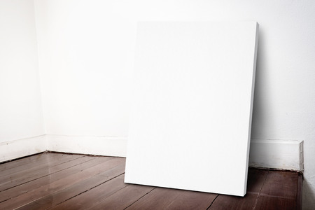 Blank white canvas frame leaning at house wall and dark brown parquet floor, Mock up for adding your design.