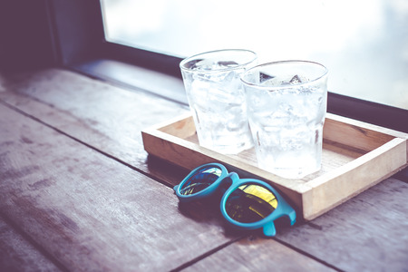 Vintage filter,sunglasses and cold glass of water on wood tray at window of restaurant.