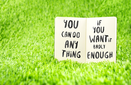 Inspiration quote :  You can do anything if you want it badly enough on notebook on grass ,Motivational typographic.