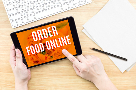 Finger click screen with Order food online word with keyboard on wooden table,Food business design concept.