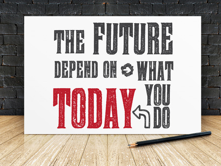 Photo pour Inspiration quote : The future depend on what you do today on white frame in black brick wall and wooden flooring ,Motivational typographic. - image libre de droit