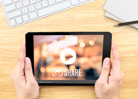 Photo for Hand holding tablet with Video sharing on screen on wood table ,Internet marketing concept - Royalty Free Image