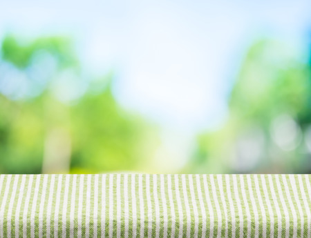 Photo pour Empty green stripes tablecloth with sun and blur green tree bokeh background, Template mock up for montage of product. - image libre de droit