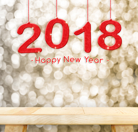 Photo pour 2018 Happy new year hanging over plain wood table top with blur gold sparkling bokeh light,Holiday concept,leave space for adding your design. - image libre de droit