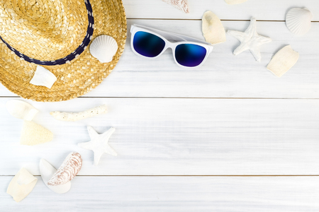 Summer Beach accessories (White sunglasses,starfish,straw hat,shell) on white plaster wood table top view,Summer vacation concept,Leave space for adding text.