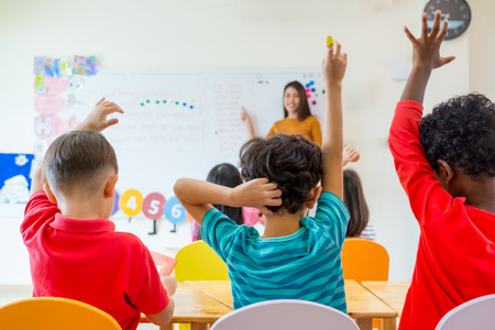 Foto de Preschool kid raise arm up to answer teacher question on whiteboard in classroom,Kindergarten education concept. - Imagen libre de derechos