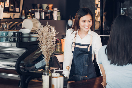Photo pour Asian woman barista wear jean apron holding coffee cup served to customer at bar counter with smile emotion,Cafe restaurant service concept,Owner small business concept. - image libre de droit