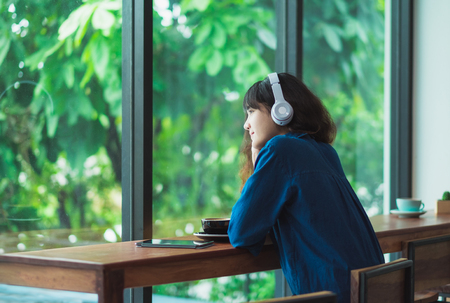 Photo pour Happy asian casual woman listening music with headphones near window at cafe restaurant,Digital age lifestyle,chill out  life. - image libre de droit