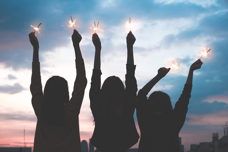 Foto de silhouette happy group of asia girl friends enjoy and play sparkler at rooftop party at evening sunset,Holiday celebration festive,teeage lifestyle,freedom and fun - Imagen libre de derechos